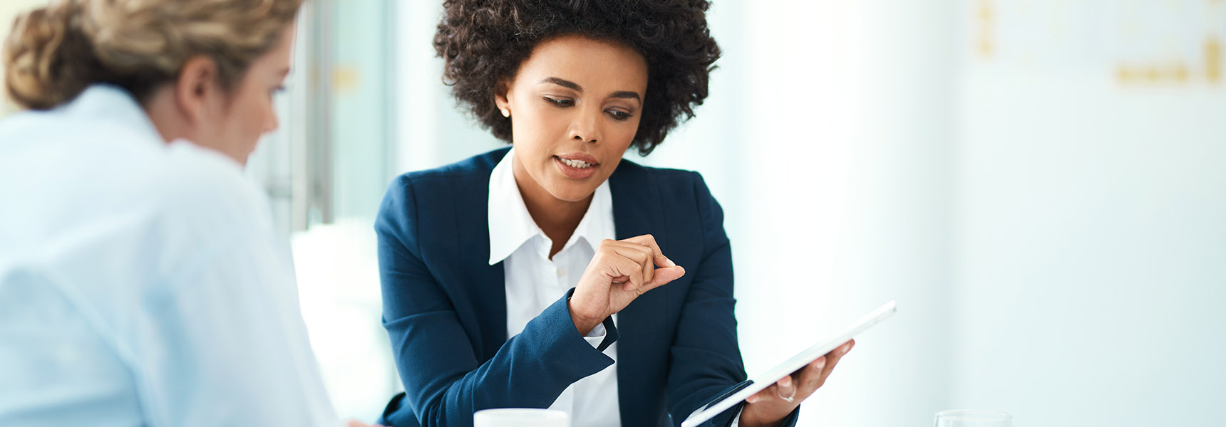 Photo of two women reviewing information.