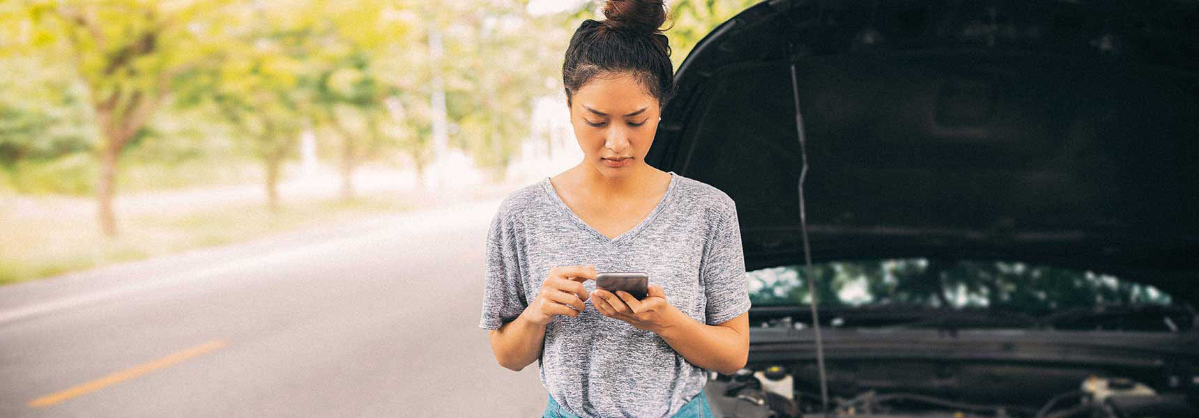 Photo of a woman with a broken down car.