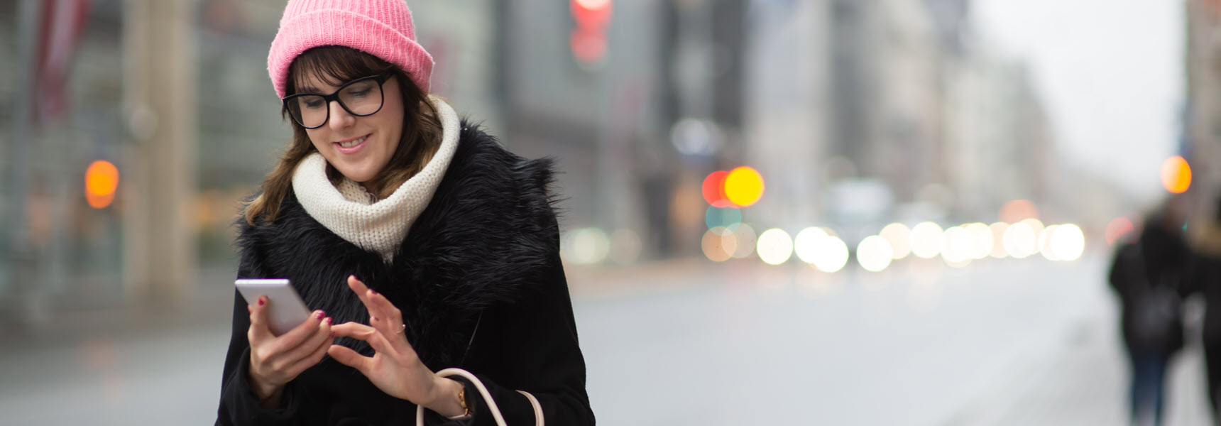 woman in winter coat and pink hat reading about the economic outlook for 2020
