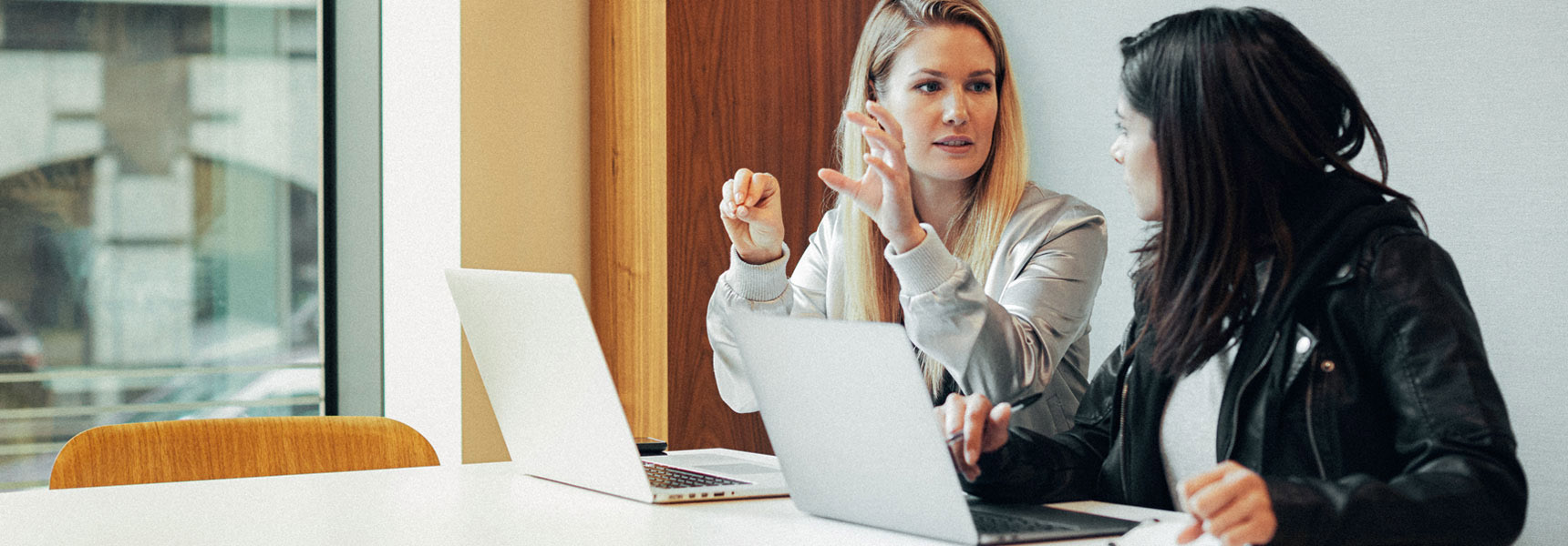 Photo of two women reviewing something on a computer.