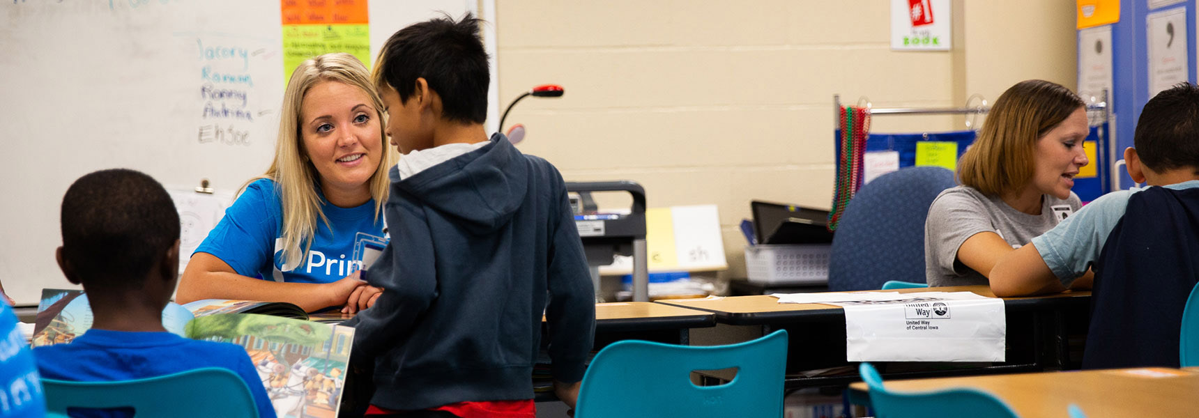 Photo of a Principal employee volunteering in a school.