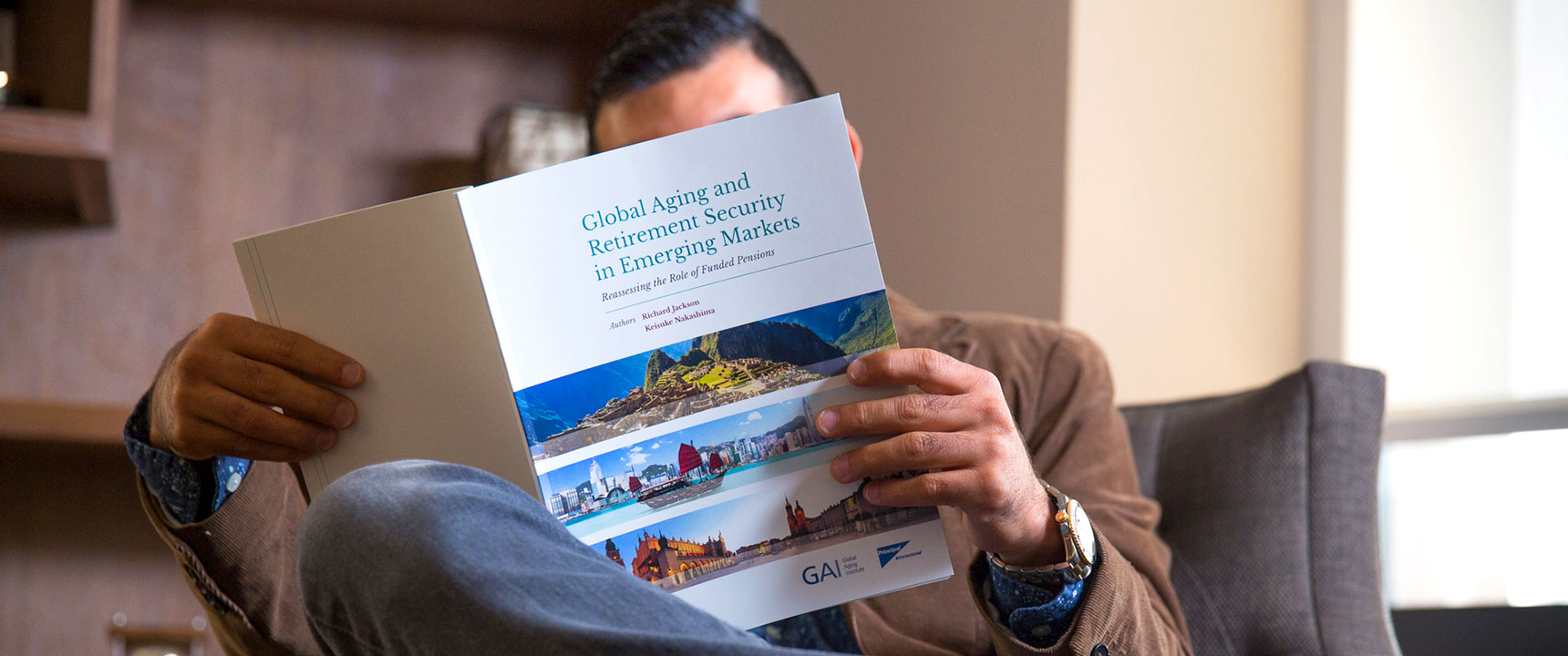 Photo of a man reading the Principal Global Aging Report.