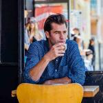 Photo of a man drinking coffee in a coffee shop.