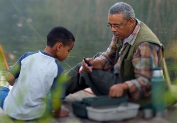 Grandfather thinking about his retirement while fishing with grandson.