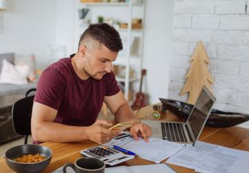 Photo of a man researching different methods to pay off debt.