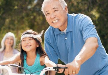 Photo of an older man helping a young child ride a bike.