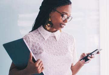 Photo of woman reviewing her 2020 financial calendar on her smartphone