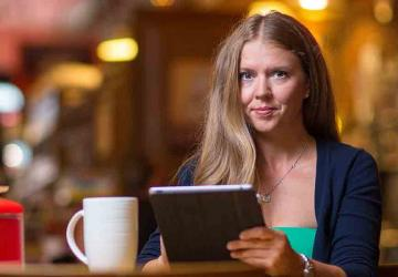 Woman sitting in a coffee shop using her tablet.