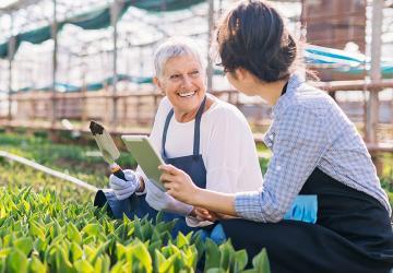 Women enjoying gardening in a greenhouse.
