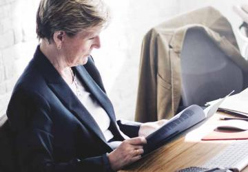 Photo of a woman sitting at a desk in an office environment.