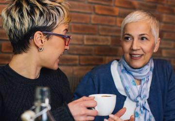 Two women sitting in a coffee shop talking about social security.