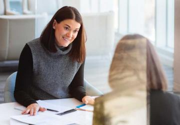 A woman talking to her female advisor.