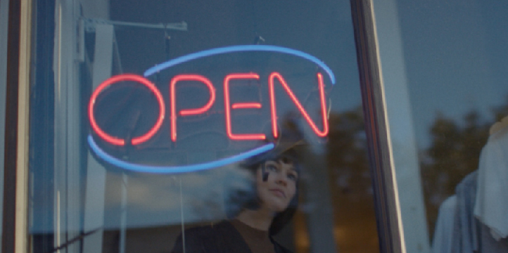 Photo of a business owner opening their store for the day.