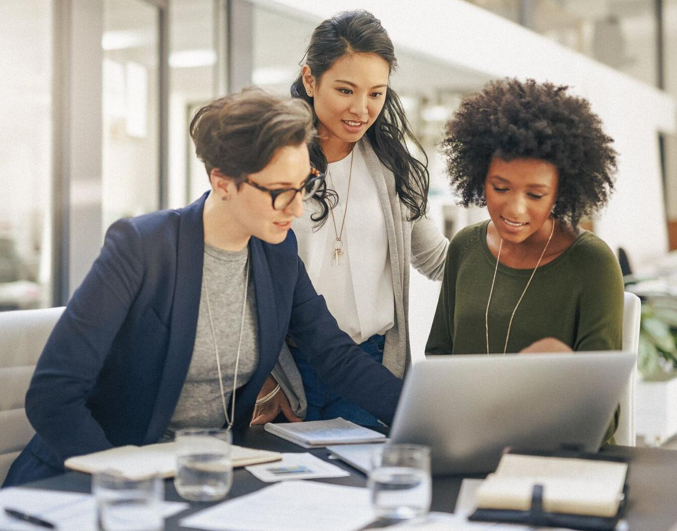 Picture of three woman working at a conference table.