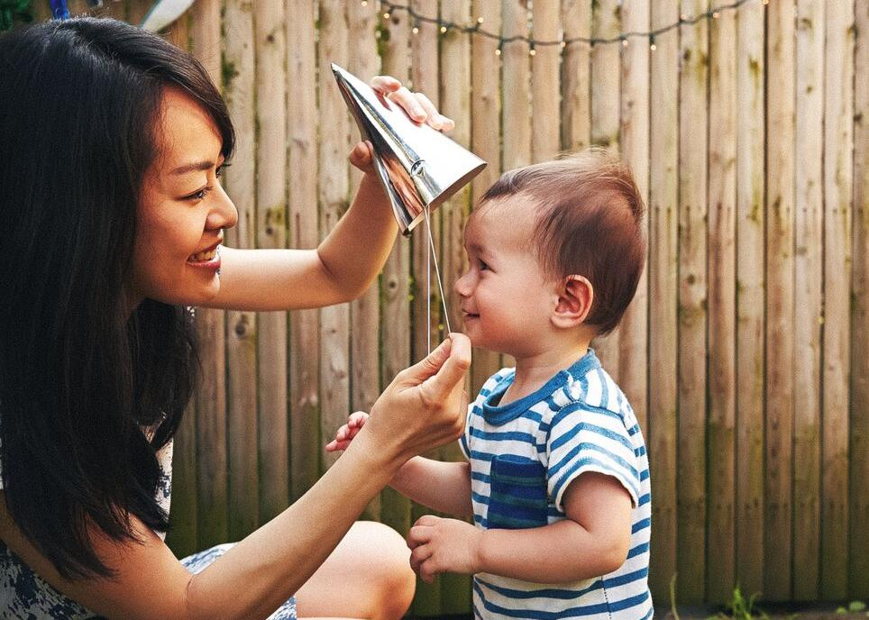 Picture of a woman putting a party hat on a small child.