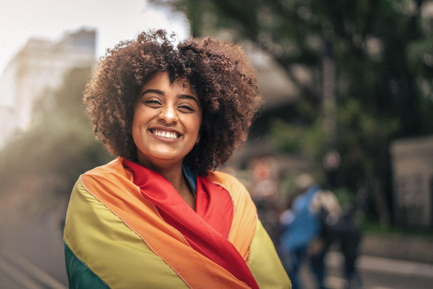 Photo of a woman with a rainbow flag.